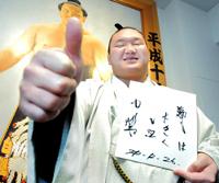来年の目標を記した色紙を手に笑顔を見せる白鵬
