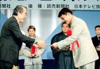 昭和シェル石油・鹿島賢治常務取締役(左)からガソリン1年分の目録を手渡される丸山