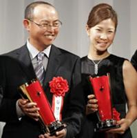 表彰式でトロフィーを手に笑顔の上田と谷口徹(左)