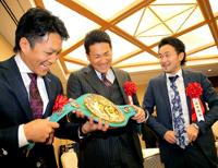 山中(右)のチャンピオンベルトに触り、笑顔を見せる田中(左は則本)