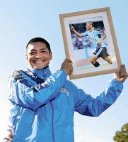 今季23ゴール目を決めた写真を手に笑顔の川崎・大久保